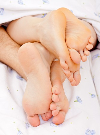 Close-up of  couples feet on bed photo