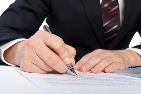 Close up of human hand signing a document