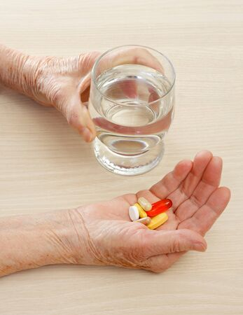 Close-up of aged hands taking the pills photo