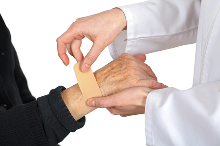 Picture of doctors hand giving an adhesive plaster for an elderly hand photo