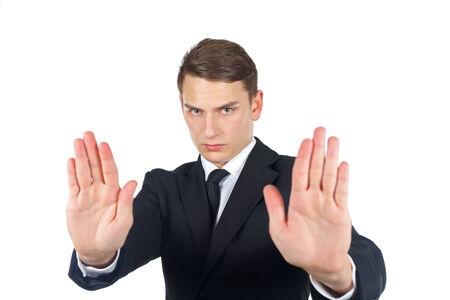 Serious businessman making stop gesture on isolated