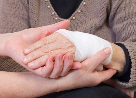 Picture of doctors hand making a bandage for an elderly hand photo