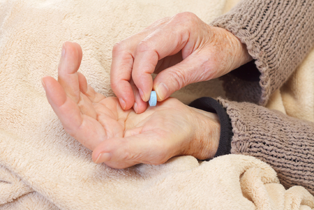 Close up of an elderly hand holding pills photo