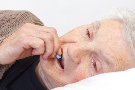 Close up of an elderly eating holding in her bed photo