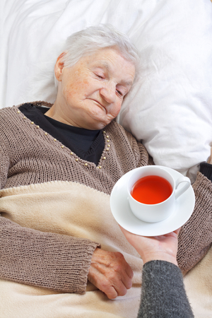 Picture of a woman hand giving tea to an elderly woman photo