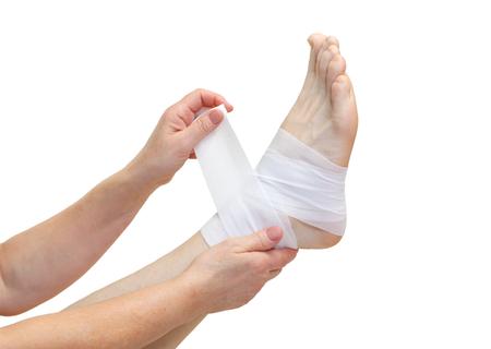 Verpleegkundige bandages een gebroken enkel geïsoleerde Stockfoto