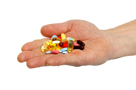 Close up of adult hands holding colorful pills photo