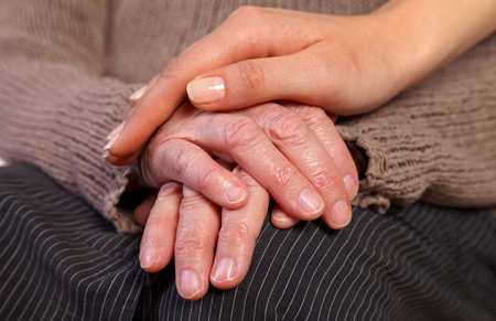 Nurse holding elderly wrinkled hand photo