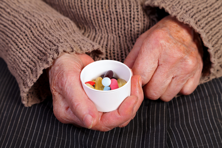Close up of an elderly hand holding a box with pills photo