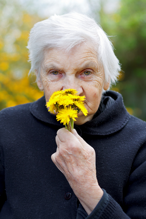 aiding: Picture of an elderly woman holding a yellow flower