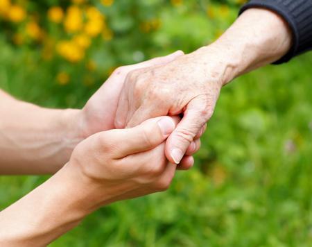 医師の手をしわくちゃ老人の手を握って