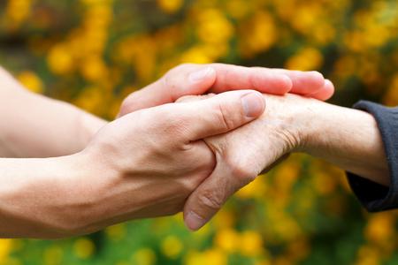 Arzt Hand, die eine faltige ältere Hand Standard-Bild