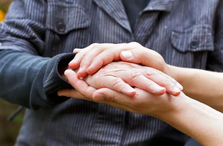 Doctor's hand holding a wrinkled elderly hand 免版税图像