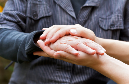 Doctor's hand holding a wrinkled elderly hand Stock Photo