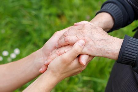 enfermera con paciente: Mano del doctor que sostiene una mano mayor arrugada
