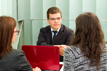 Confident businessman talking with his clients in the office photo