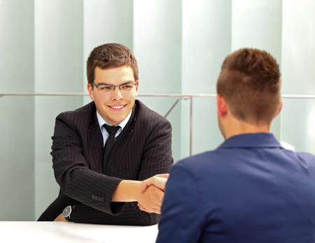 Confident businessman talking with his client in the office photo