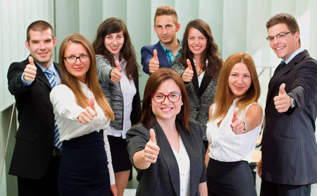 thump: A business team standing in office after a successful business with thump up
