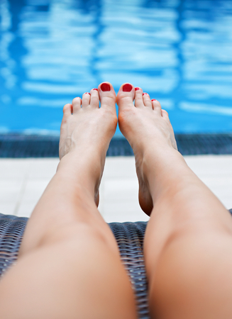 Woman relaxing at the side of the pool photo