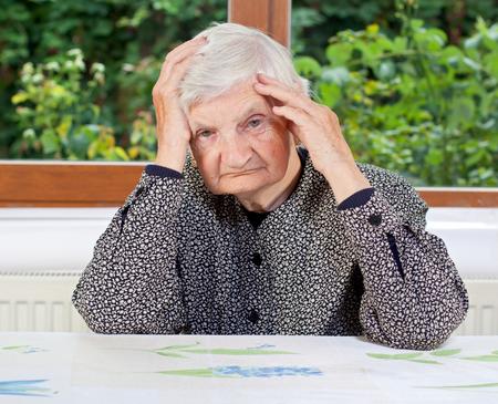 Ongelukkige oudere vrouw zitten aan de tafel