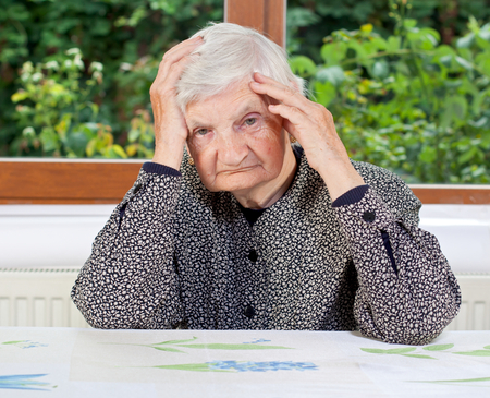Unhappy elderly woman sitting at the table