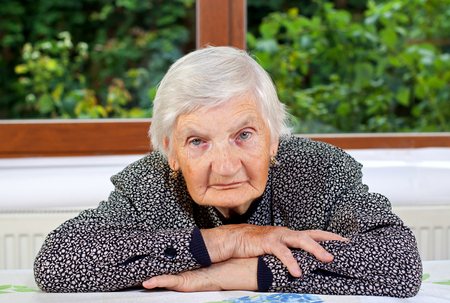 aiding: Unhappy elderly woman sitting at the table