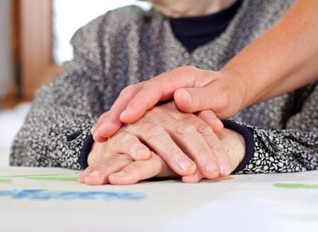 Hand van de arts houden van een gerimpelde ouderen de hand