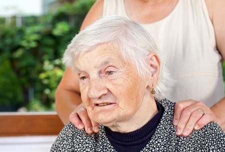 노인 환자에게 마사지를주는 간병인