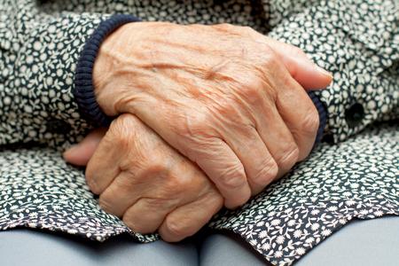 Bejaarde vrouw raakt haar gerimpelde kant