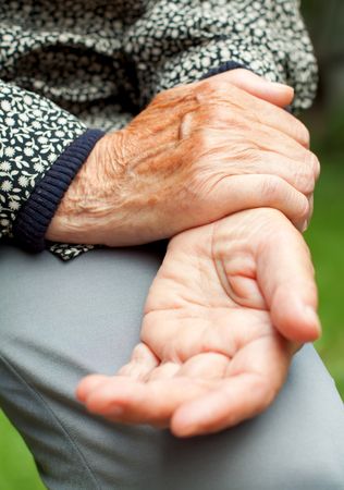 An elderly woman holding her painful wrist Stock Photo