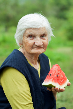 Elderly happy woman eating watermelon in the garden photo