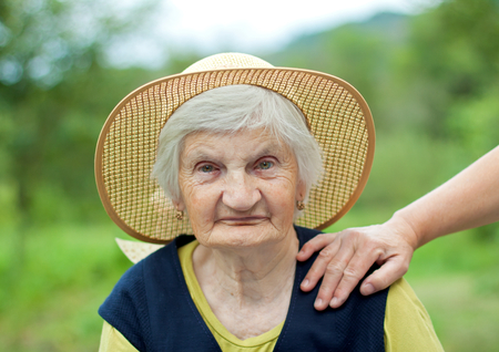 Happy elderly woman with hat in the garden photo