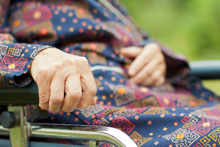 aiding: Handicapped elderly woman sitting in a wheelchair Stock Photo