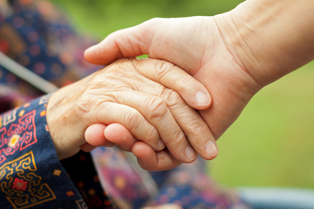 Doctor's hand holding a wrinkled elderly hand Stock Photo