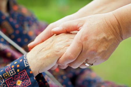 의사의 손을 주름이 잡힌 된 노인 손을 잡고