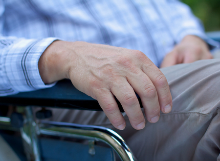 aiding: Handicapped elderly man sitting in a wheelchair Stock Photo