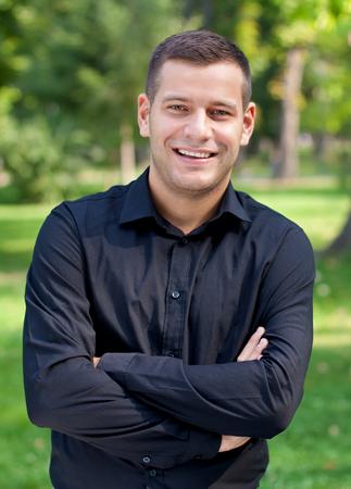 Pohledný muž v košili stojící v parku