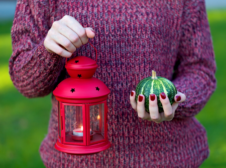 Womans hand holding a red lantern and a pumpkin photo