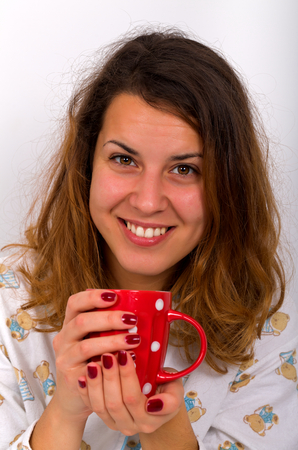 Attractive woman drinking coffee in her bed photo