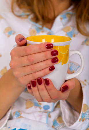Picture of a woman hand holding hot coffee mug photo