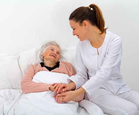 an elderly person: Mujer mayor con su cuidadora en casa