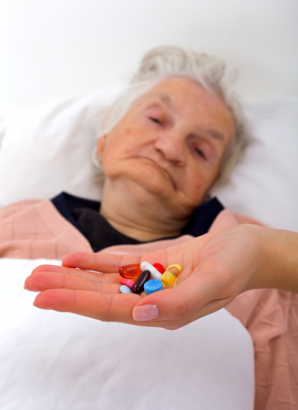 doctors with pills: Elderly woman with her caregiver at home