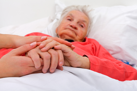 sick in bed: Elderly woman with her caregiver at home