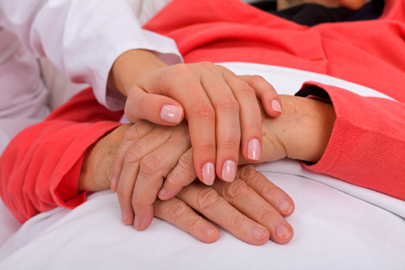home health care: Caregiver holding elderly patients hand at home Stock Photo