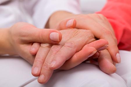 介護者の在宅高齢患者の手を握って 写真素材