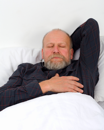 Picture of a sleeping elderly man with headache photo