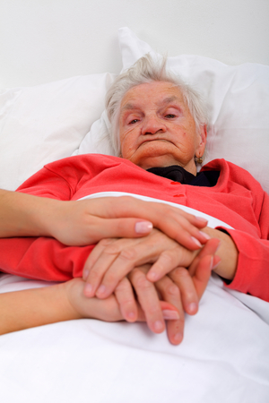 the elderly caregivers: Beautiful elderly woman holding her caregivers hand in the bed