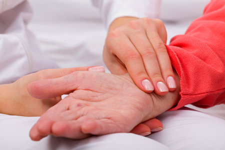 hypotension: Caregiver checking patients blood pressure Stock Photo