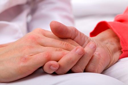Caregiver holding elderly patients hand at home Standard-Bild
