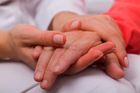 home care: Caregiver holding elderly patients hand at home Stock Photo